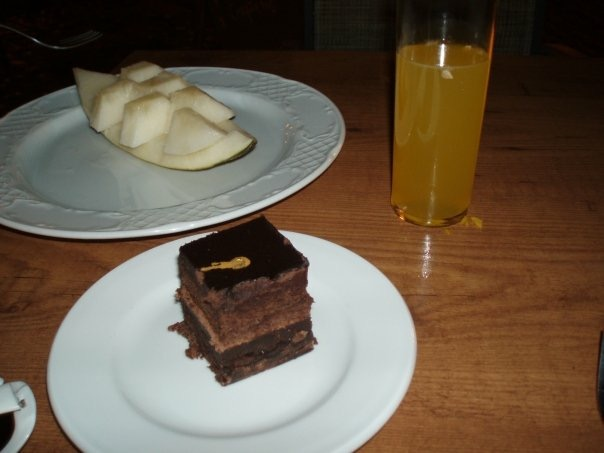 a white plate with a slice of melon, a white plate with a square chunk of chocolate cake and a tall glass of vodka and orange