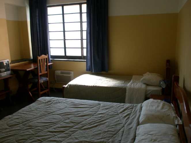 Photo of a hostel room with yellow walls, 2 double bed, a table and chair, TV and ac under a large window.