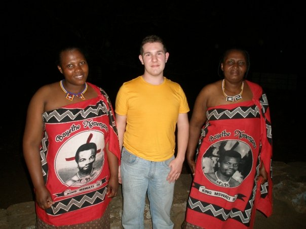 Karl poses for a photo between 2 women from Swaziland who are wearing red wrap around dresses