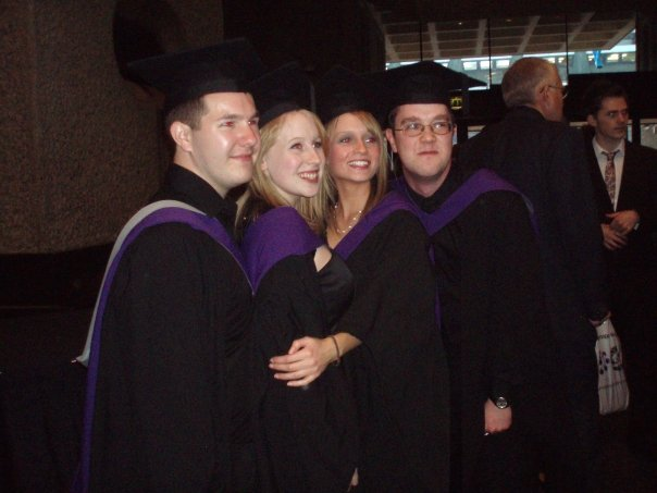 Karl, Rosie, Kim and Andrew in their graduation robes stand close together and pose for a photo