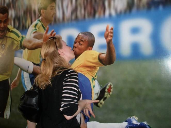 Rosie pretends to kiss a footballers picture at the Maracana Stadium, Rio de Janeiro