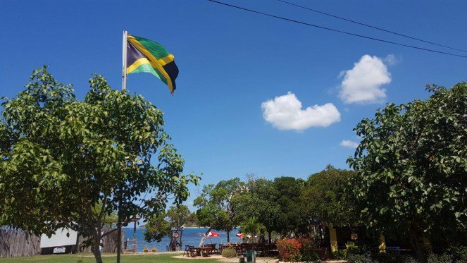 The Jamaican flag flies in a blue sky above Jack Sprats bar in Treasure Beach, Jamaica