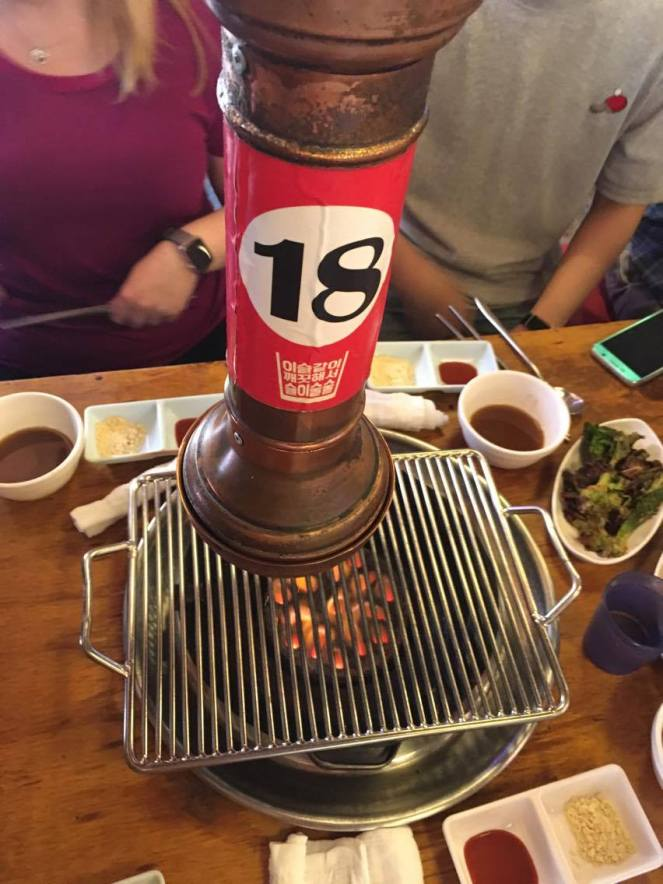 a metal cylindrical extractor fan above a bowl of coals with a metal grill in the centre of a table in a Seoul restaurant, South Korea