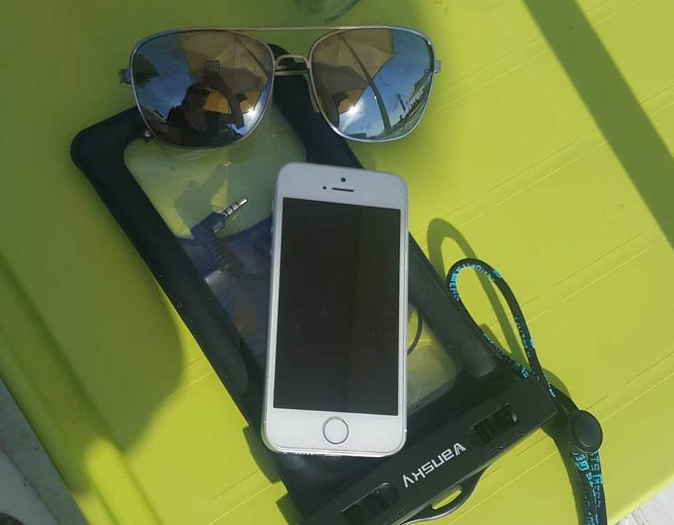 A photo of a white iphone, sunglasses and a waterproof pouch on a plastic green table