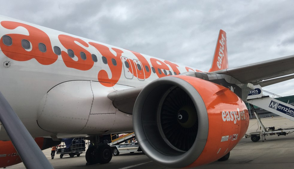 A photo of an easyJet Airbus plane body and engine from the bottom of the boarding stairs