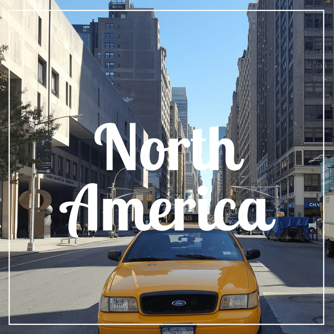 North America written over a photo of a yellow New York Taxi in the foreground on a street with tall buildings either side