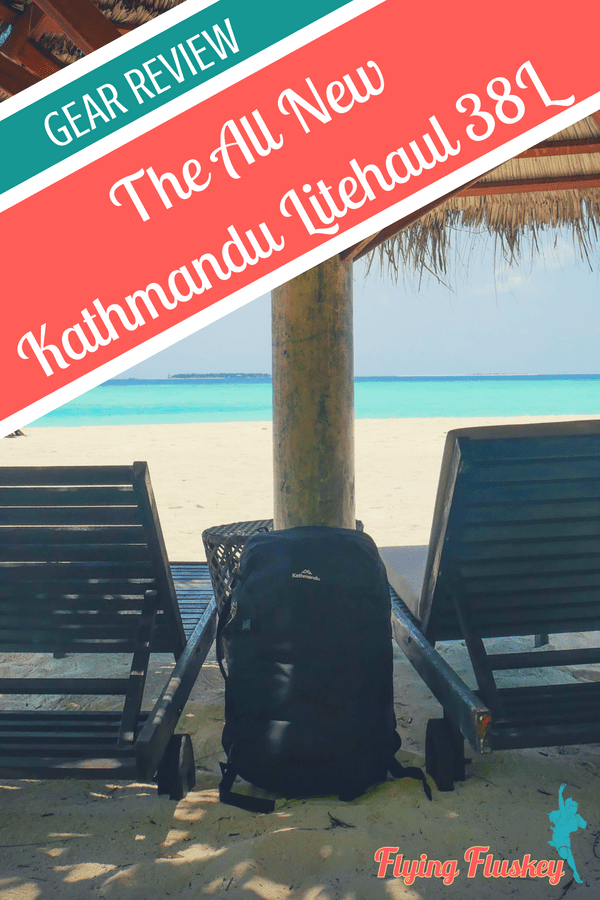 a black Kathmandu Litehaul 38L Backpack propped against a straw parasol on a white sandy beach in the Maldives. White text on a red banner in the top left corner reads 'The All New Kathmandu Litehaul 38L'
