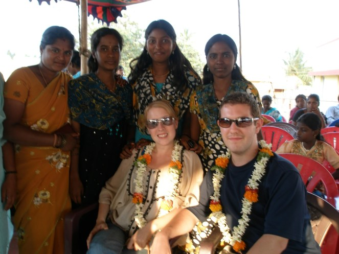 Karl & Rosie sit with flower garlands with 4 young Indian ladies posing behind in Kolar Gold Fields