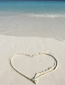 a love heart drawn in the white sand on a a beach in the Maldives