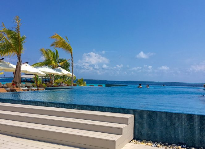 blue infinity pool overlooking the sea at Kihaa Maldives
