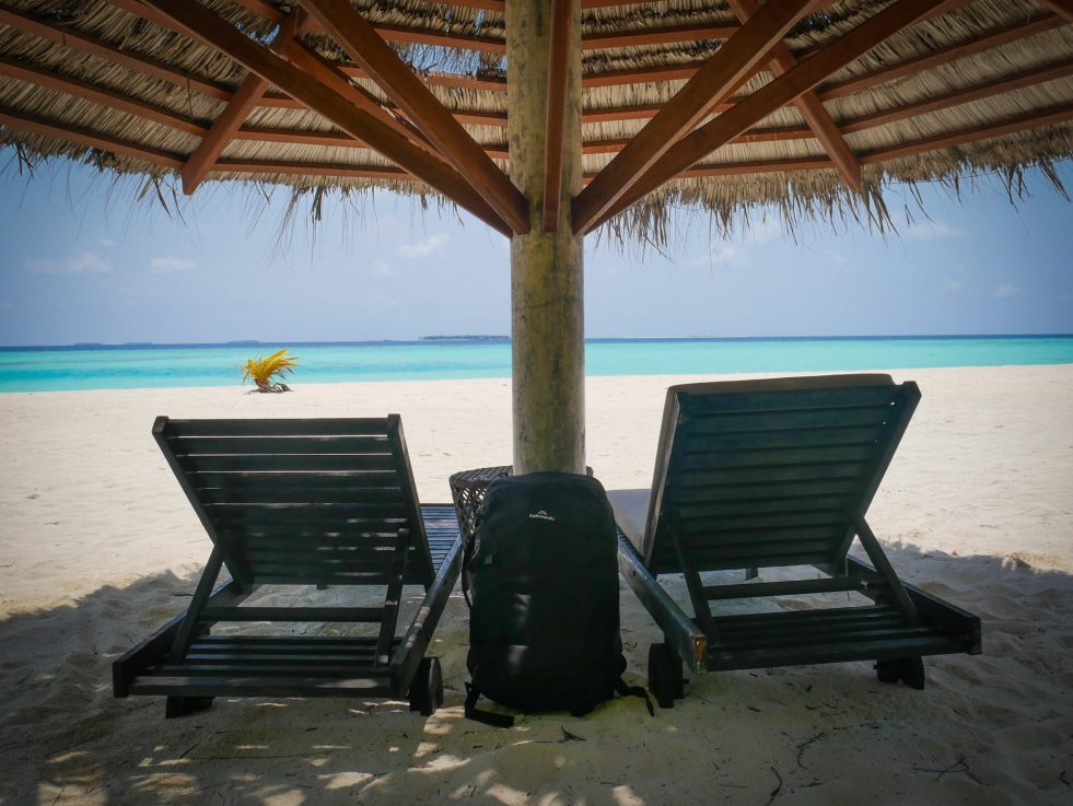 a black Kathmandu Litehaul 38L Backpack propped against a straw parasol on a white sandy beach in the Maldives