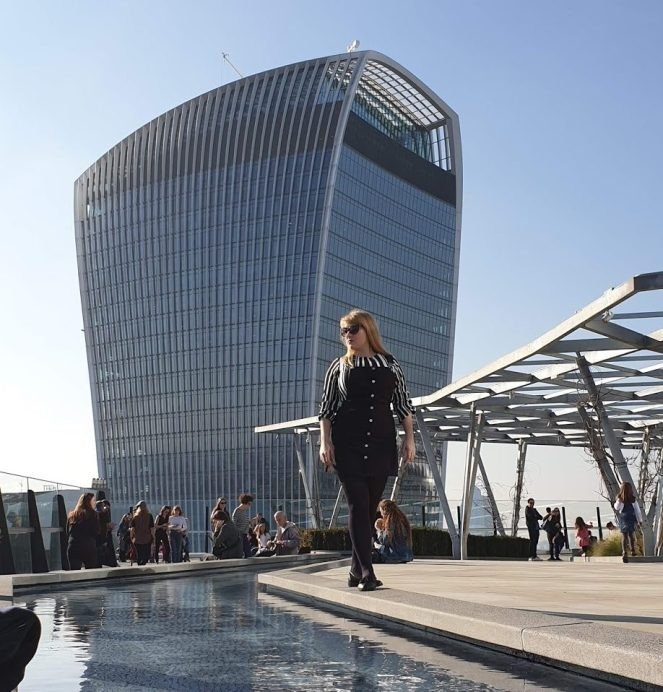 Rosie standing on the edge of a pool in front of 20 Fenchurch Street building