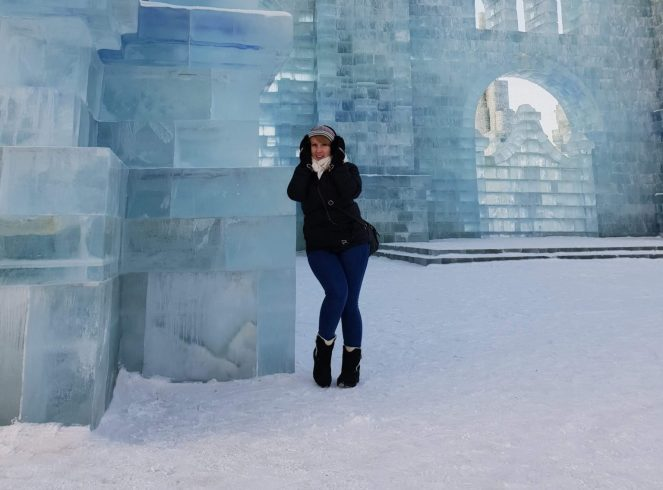 Rosie leans against an ice building wearing a coat and earmuffs at Harbin Snow and Ice Festival