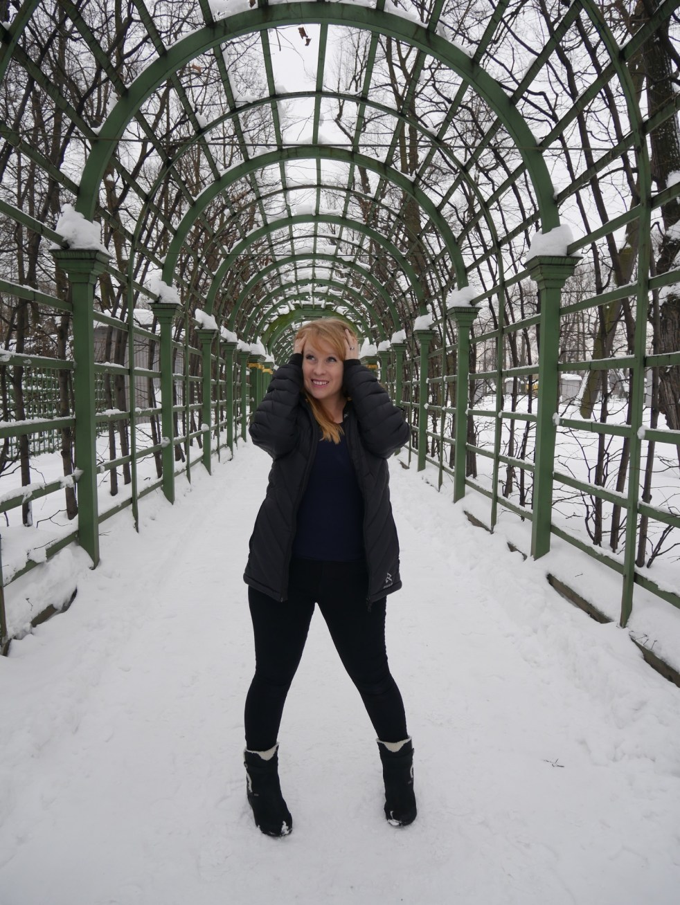 Rosie standing in snow under an arbor wearing a black Ravean Down X Heated Jacket