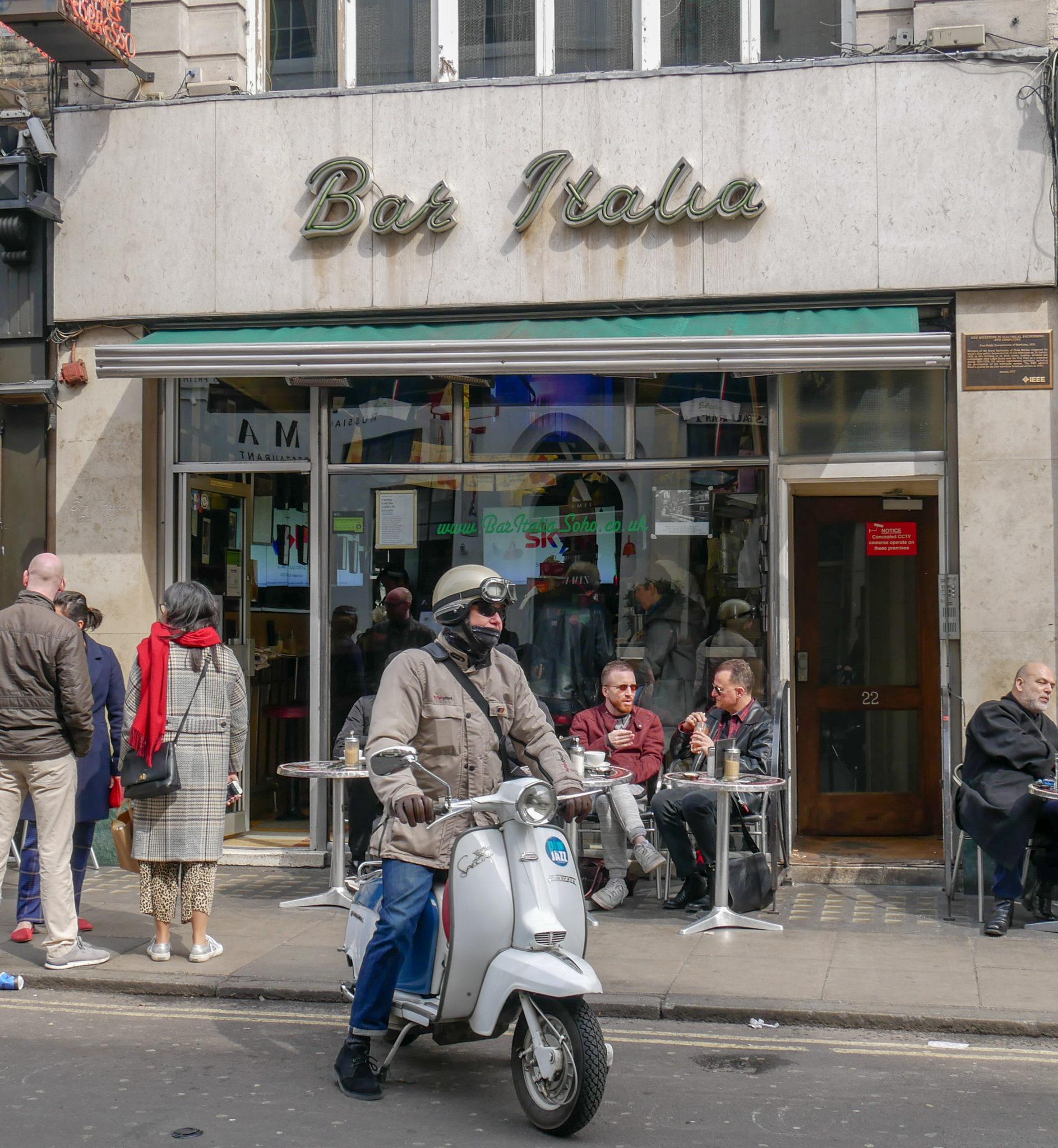 a man on a Vespa in front of Bar Italia, Soho, London