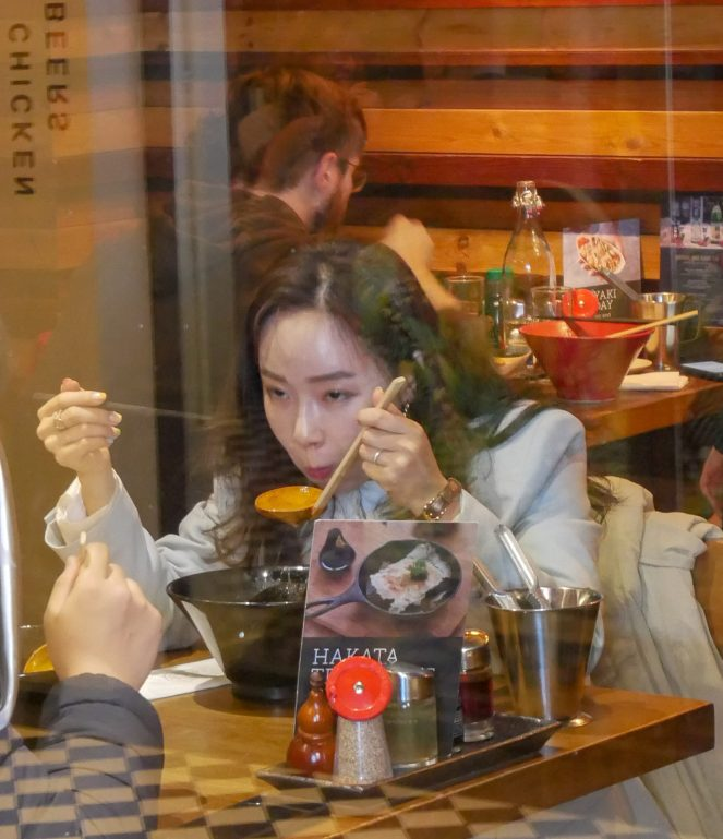 an Asian woman blows on a wooden ramen ladle with chopsticks in her other hand at Shoryu Japanese restaurant, Soho, London