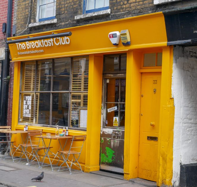 The yellow walls, door and sign of The Breakfast Club, Soho, London
