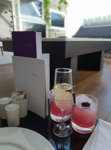 a glass of champagne and and two red cocktails on a table in the Virgin Atlantic Clubhouse London Heathrow Airport Terminal 3