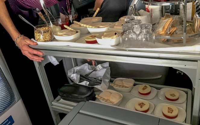 metal dessert trolley with bowls of ice cream and plates of cheescake on Delta One Delta Air Lines