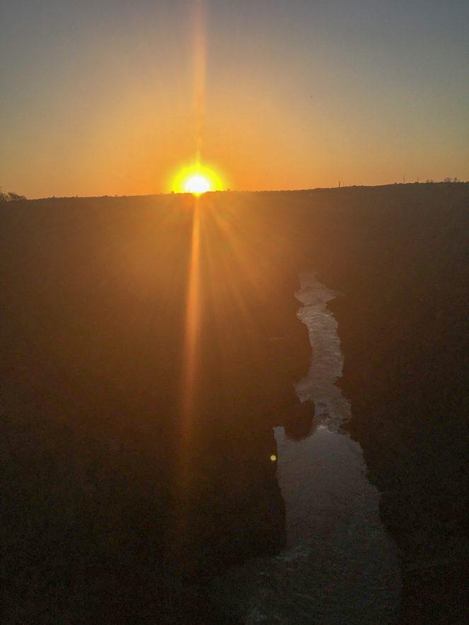 The sun sets over the Victoria Falls gorge