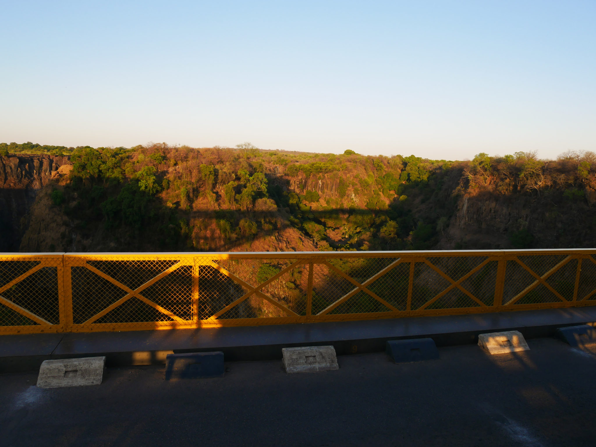 The setting sun casts a shadow of the Victoria Falls Bridge on the gorge