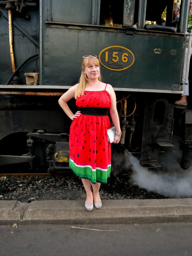 Rosie stands in a red dress by the side of the Royal Livingstone Express steam engine 156