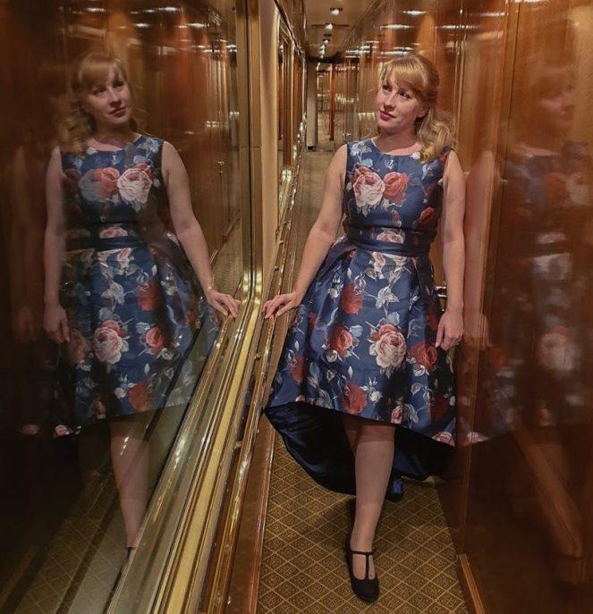 Rosie in a blue dress walks the corridor on The Blue Train