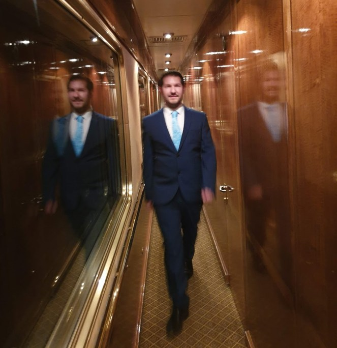 Karl in a suit and blue tie, walks the corridor on The Blue Train