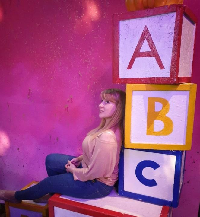 Rosie leans against giant children's alphabet clocks. She has a weird smile.