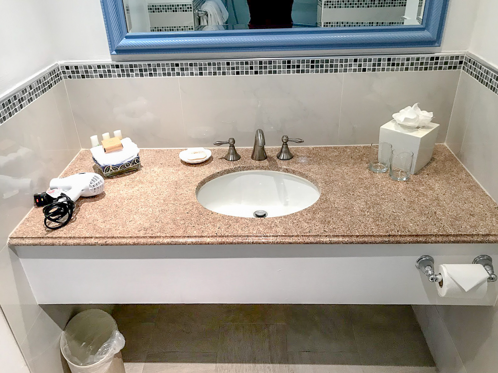 The Club Barbados sink and surrounding counter. It is a warm marble colour
