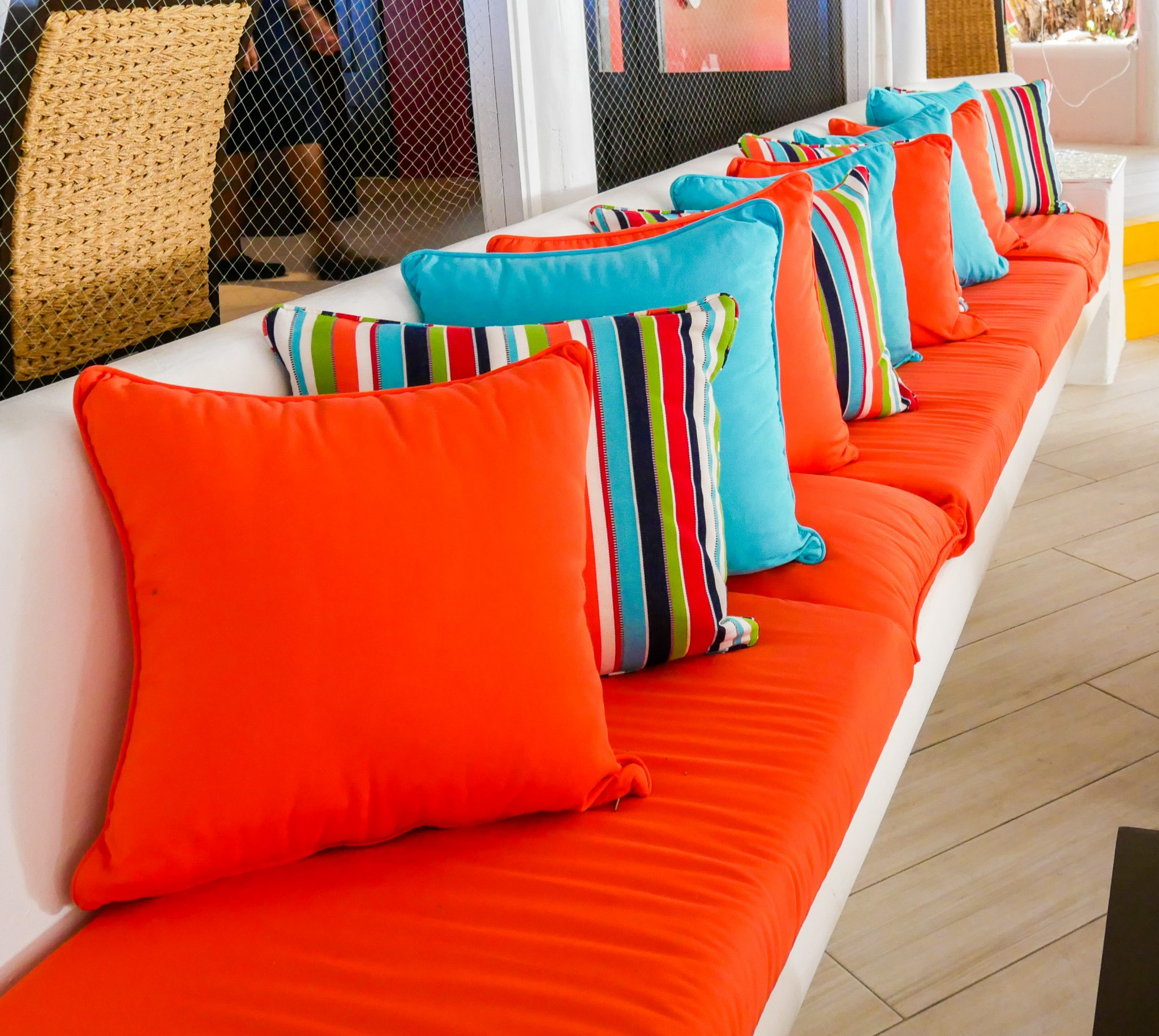A long beach with lots of orange cushions