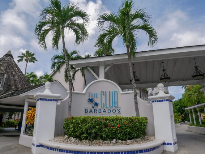 Th Club Barbados entrance sign with two palm tress behind it
