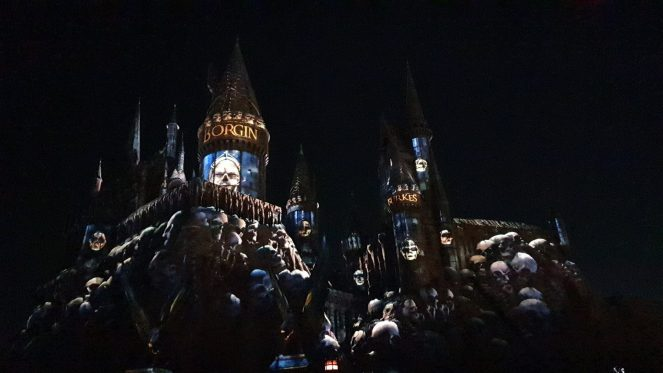 Skulls and signs for Borgin and Burke are projected on Hogwarts