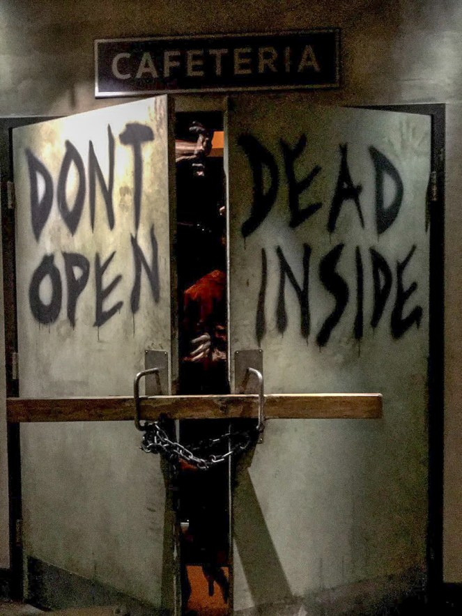 Zombies coming through a door that says Don't Open Dead Inside