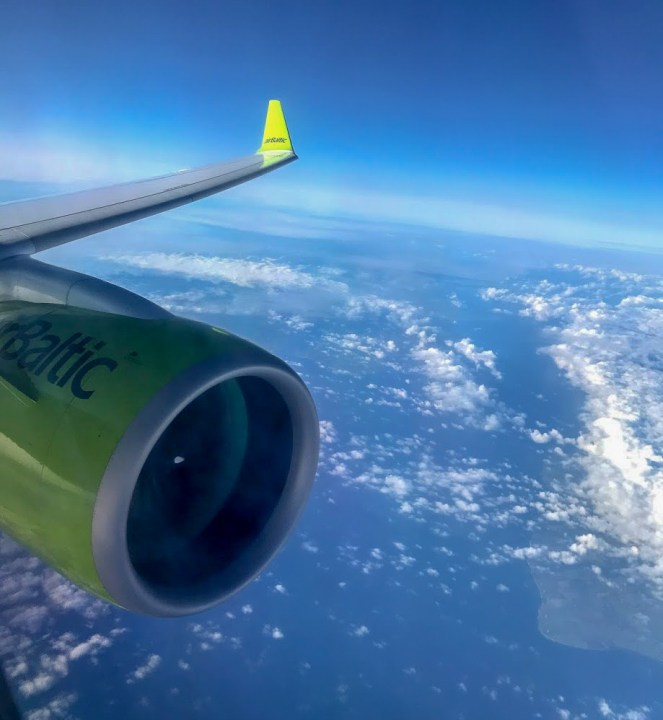 wing and engine of an airBaltic A220-300 above the clouds