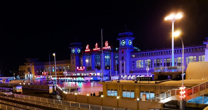 Beijing train station from the outside, by night. The station is in lit in garish blue light.