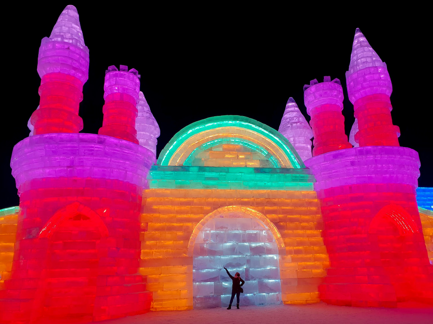 Rosie standing in front of a multicoloured ice castle building at Harbin Ice and Snow World