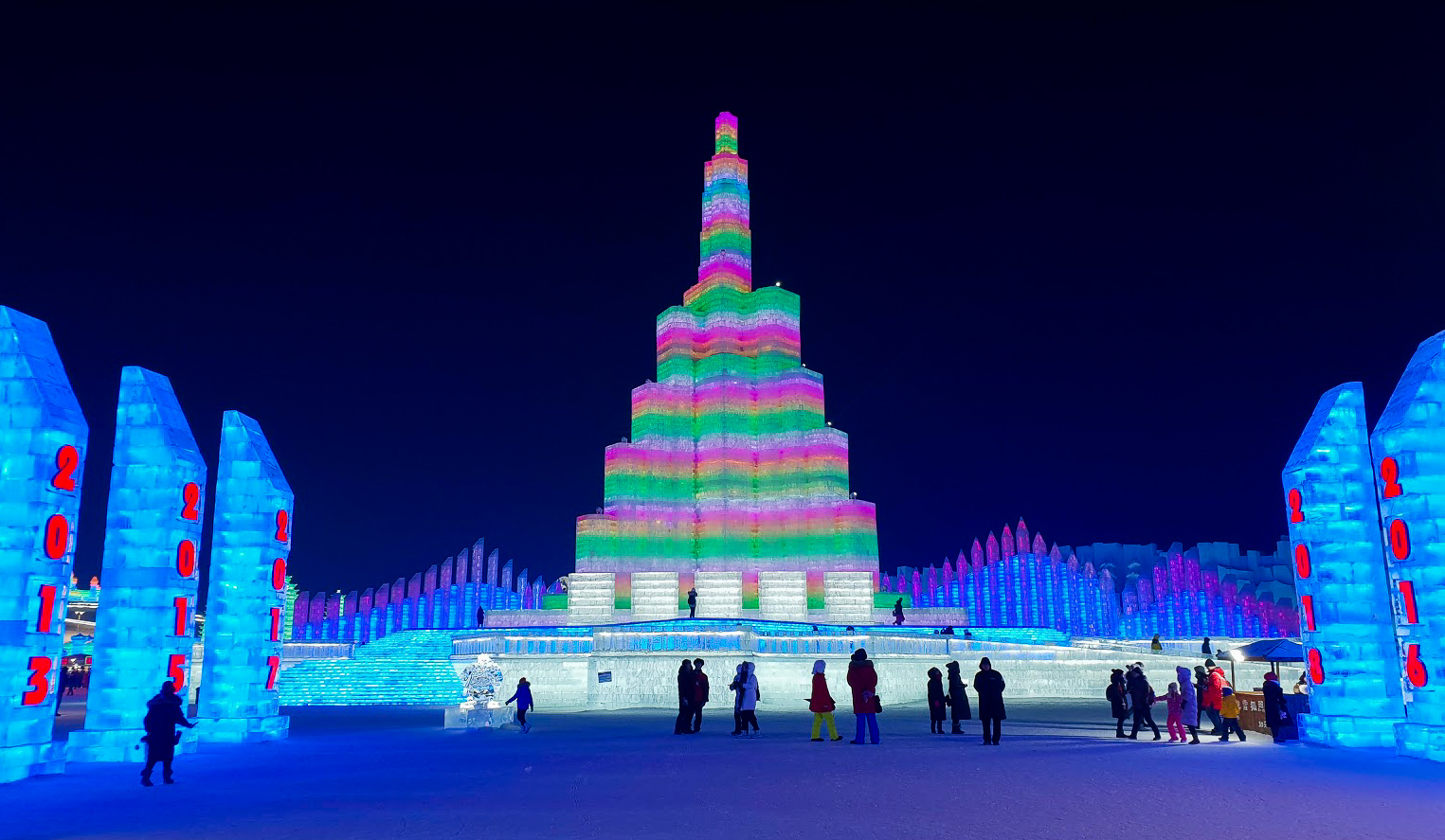 a multicoloured ice tower at Harbin Ice and Snow World