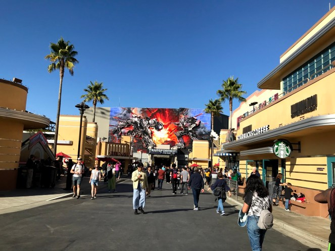 People walk along the Lower Lot in front of the TRANSFORMERS: The Ride-3D in Universal Studios Hollywood