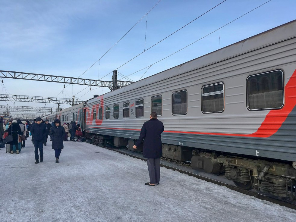 A Trans-Siberian train on a busy platform in Russia