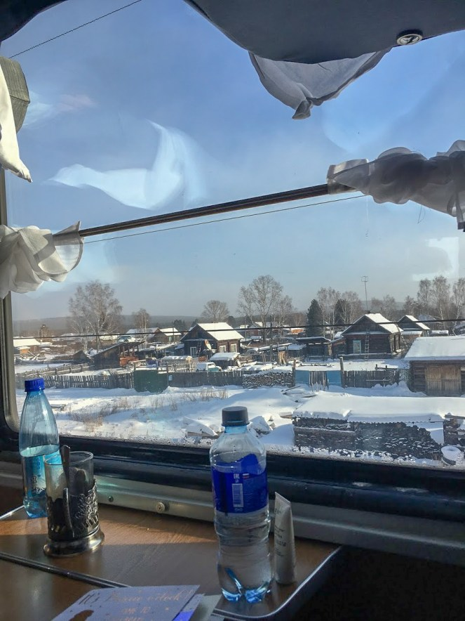 Houses covered in snow from the window of a Trans-Siberian Train
