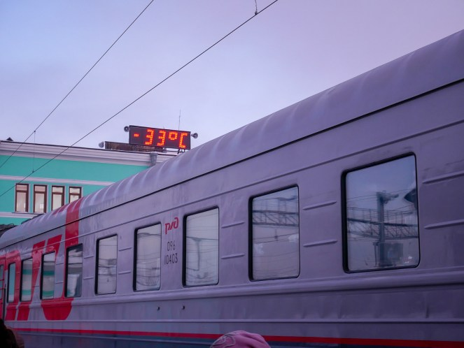 An electronic display shows -33°C at at station above a Trans-Siberian Train