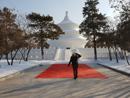 Rosie in front of an ice building at the Harbin Ice & Snow Festival, China