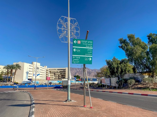 A green direction sign before a roundabout in Eilat, Israel