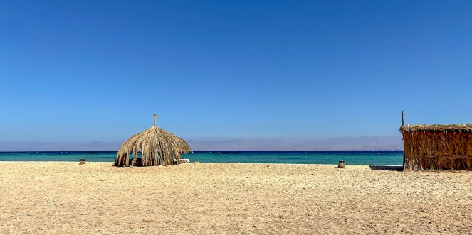 a sandy beach with a palm shade and a palm hut in the Gulf of Aqaba, Egypt