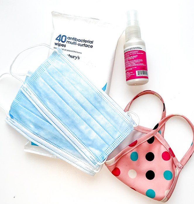 PPE - a pink spotty face mask, antibacterial spray bottle and antibacterial wipes