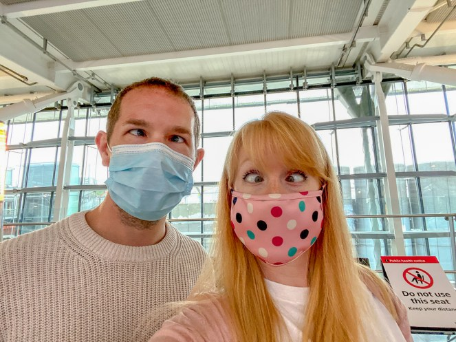Karl and Rosie wearing face masks, pulling funny faces at London Heathrow Terminal 5