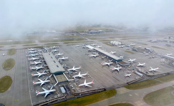 view out of a British Airways plane window of a cloudy Terminal 5 at London Heathrow