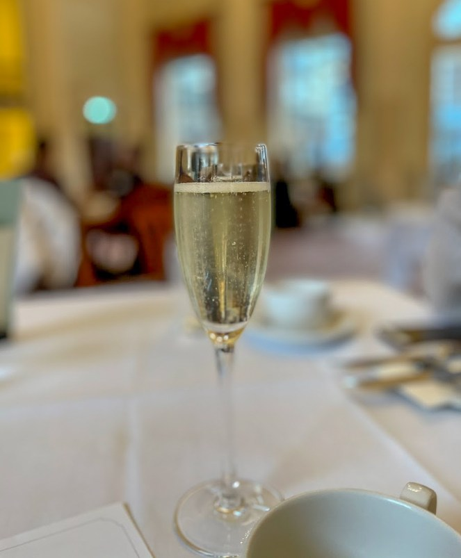 A glass of prosecco on a white table cloth in The Pump Room Bath
