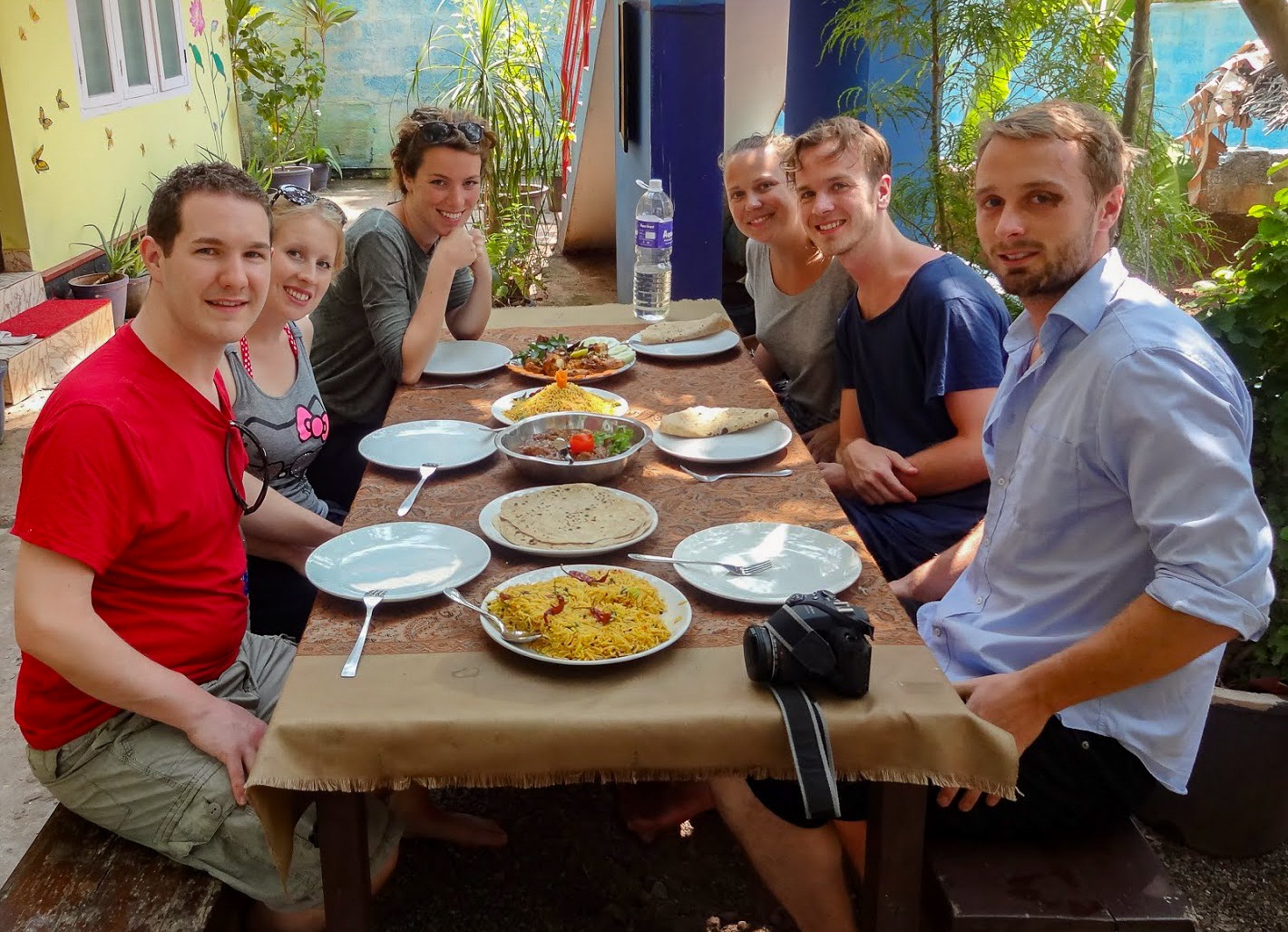 Karl, Rosie and 4 others sit around along a table with curry and rice dishes at Khan's Cooking Class, Varkala, India